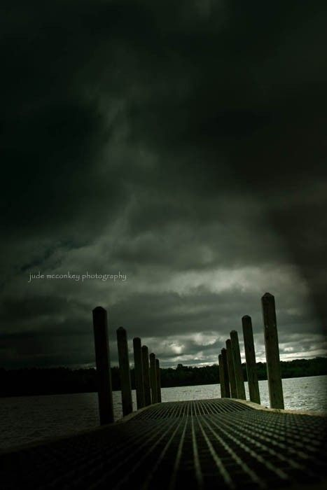 a dock on the water on a dark and storm day. Very gloomy